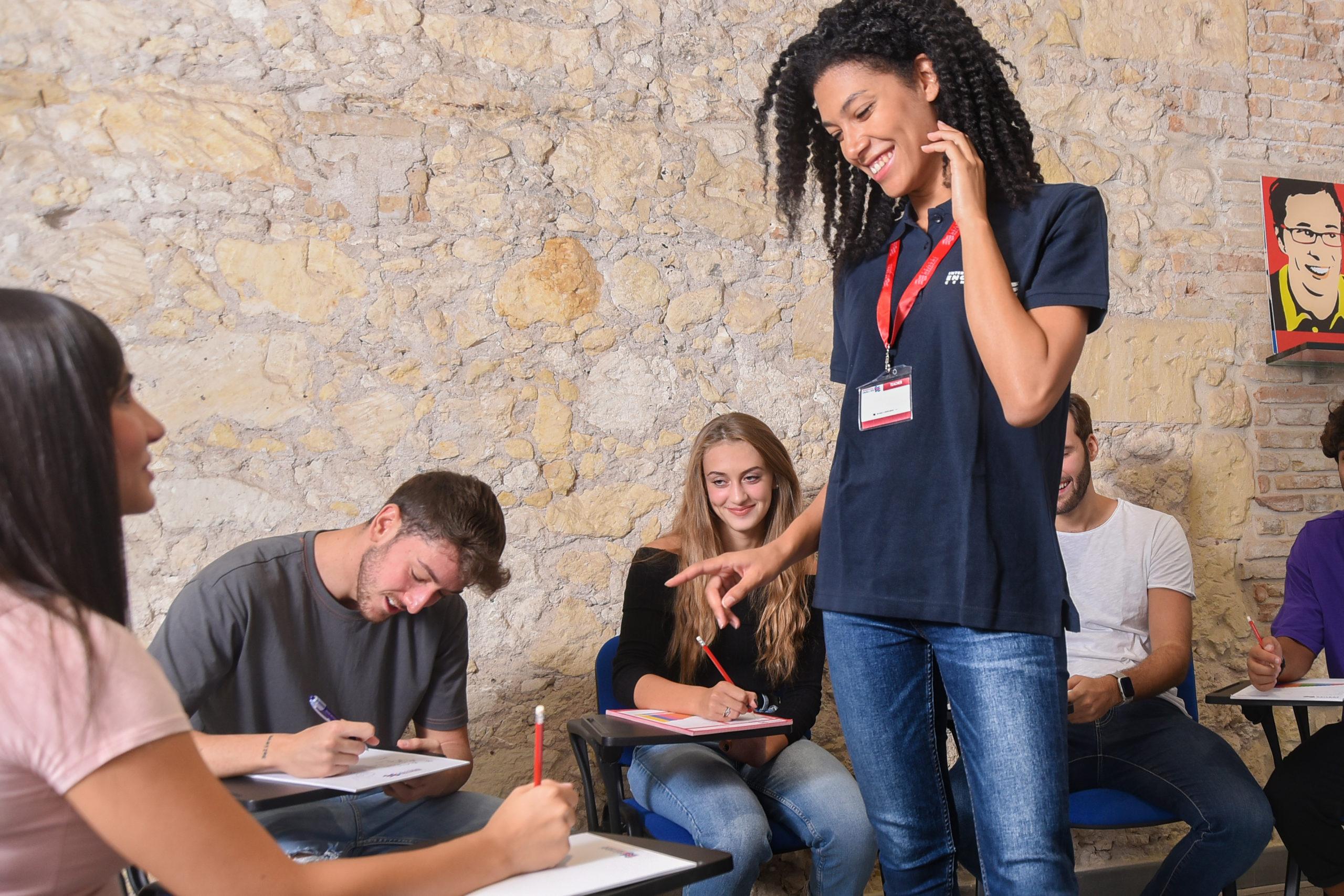 La foto ritrae una docente International English Centre in piedi al centro dell'aula durante un corso di inglese con degli studenti